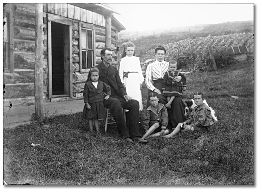 Photographie : Family group outside a log building, [vers 1900]