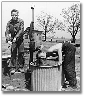 Photographie : Two men at a water pump at a farm service camp, [vers 1950]