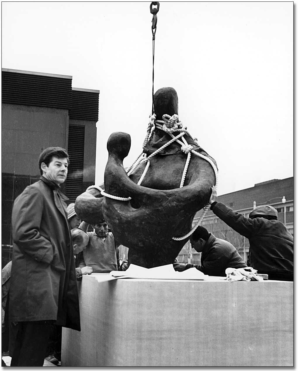 Photographie : Jack Harman supervisant l'installation de sa sculpture, Mother and Child, dans la partie ouest de l'édifice Macdonald, 1968