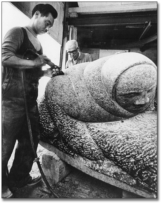 Photographie : Paulosie Kanayook travaillant sur sa sculpture, Hunter With Seal [Le chasseur et le phoque], 1968