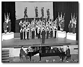 Photographie :  Eaton's employees' War Bond Rally; women on stage dressed as ordnance workers, holding flags, singing, 1943
