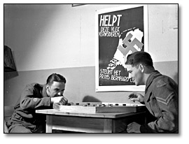 Photographie : Dutch troops playing crokinole; Dutch war poster in background, avril 1941