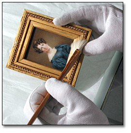 Image of framed miniature being cleaned with brush