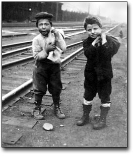 Black and white photograph of two boys near train station collecting coal from the track area