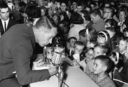 Gordie Howe speaking to children at an Eaton's sporting goods promotion event, 1964