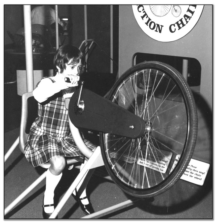 Child exploring the gyroscopic effects of a spinning bicycle wheel at Ontario Science Centre opening, September 27, 1969