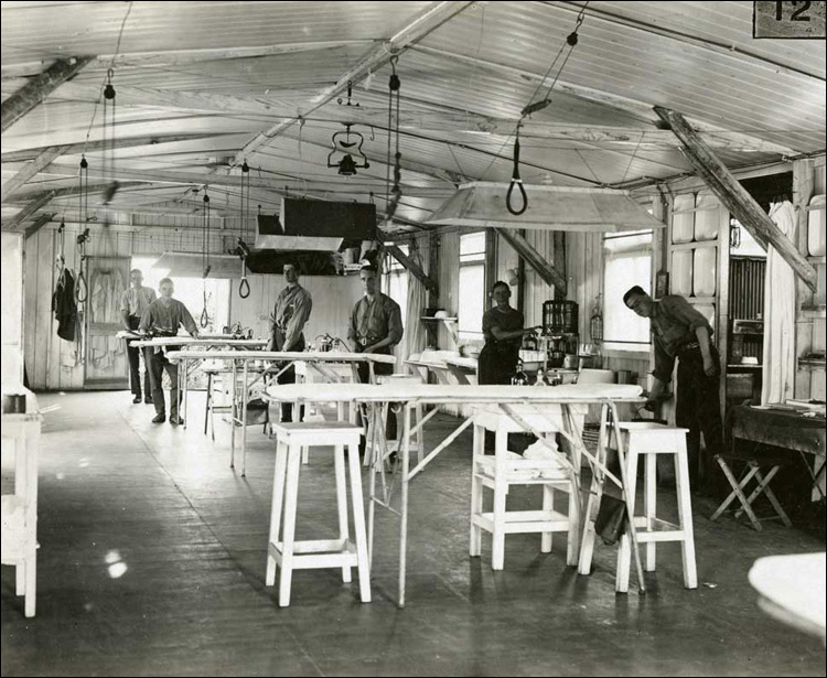 Operating theatre with slings from the ceiling to hold up legs and arms while operating, ca. 1917