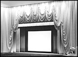Photograph of the stage, curtains and screen in an old movie theatre